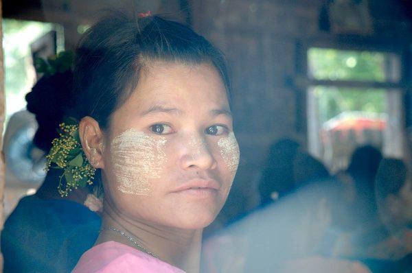 Myanmarilainen työntekijä suojaa kasvonsa auringolta kasvista saatavalla tahnalla