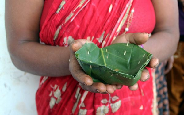 Nepalilainen nainen esittelee lehdestä tehtyä astiaa