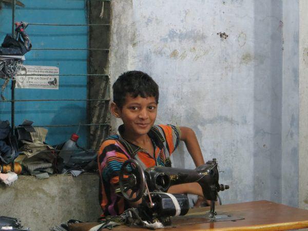 Bangladeshilainen poika ompelukoneen ääressä