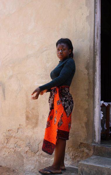 Mosambikilainen kotiapulainen kotinsa edustalla