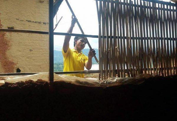 Mies rakentaa taloa Nepalissa maanjäristyksen jälkeen