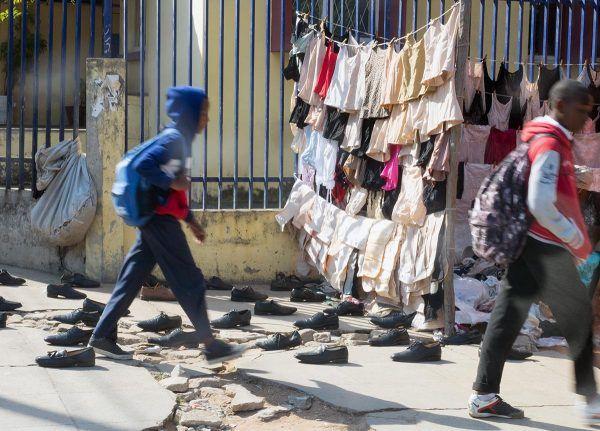 Pojat kävelevät katumyyntipisteen ohi Mosambikissa